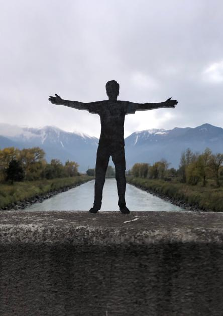 Photograph of a plastic figurine with outstretched arms with mountains in the background