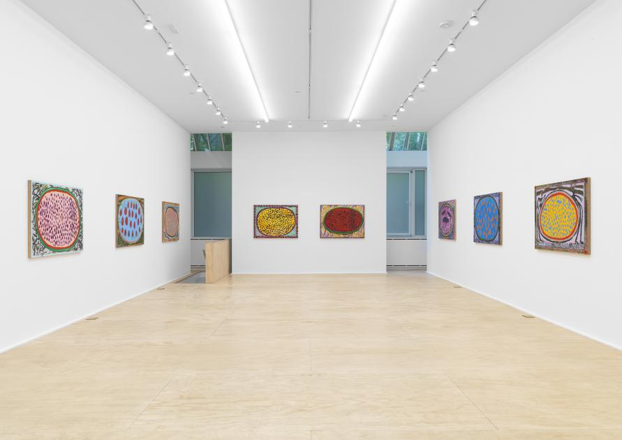 An installation view of several brightly colored watermelon paintings by Josh Smith
