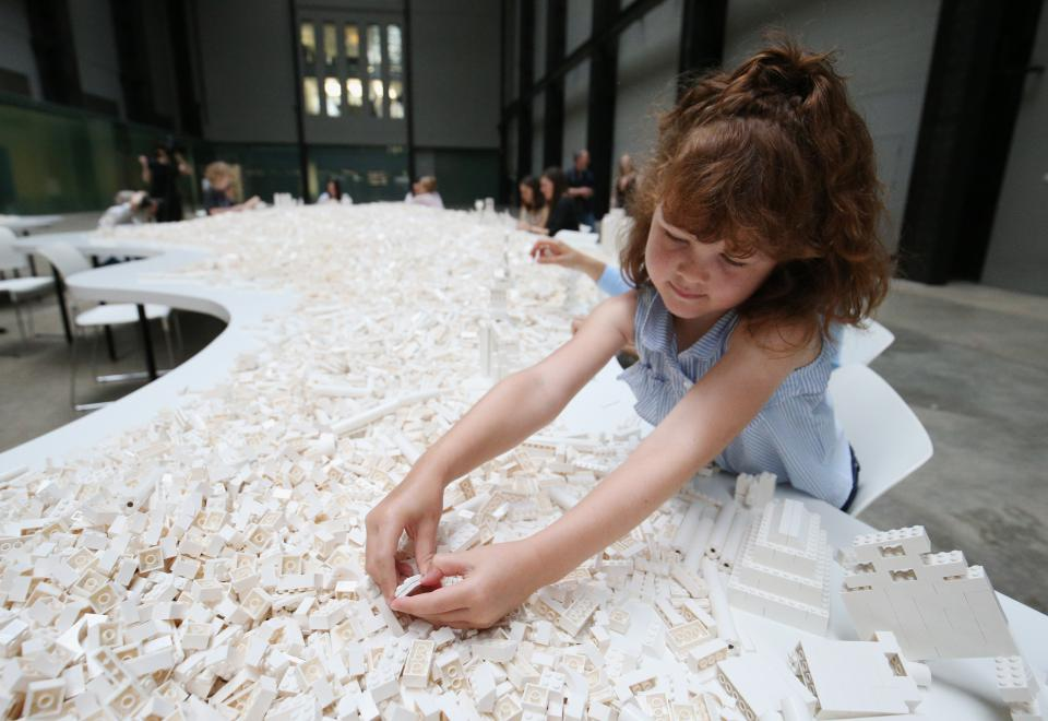 "Daisy Lenkiewicz setzt in der Turbinenhalle der Tate Modern Legosteine der Kunstinstallation ""The cubic structural evolution project"" von Olafur Eliasson zusammen"